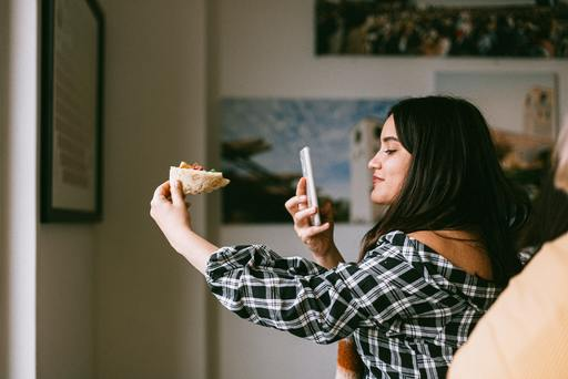 An influencer taking a picture of a local Pizza