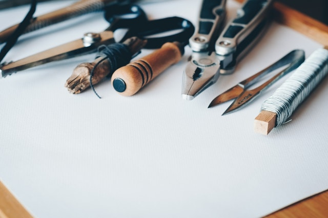 Handheld craft tools on a sheet of white paper.