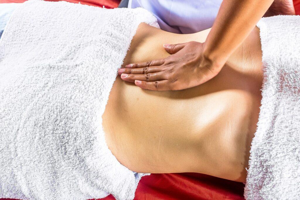 A massage technician works on a woman's back
