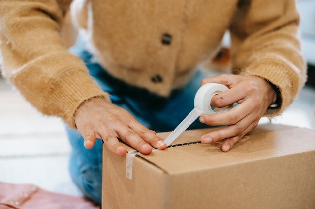 A woman boxing up one of her craft sales to ship it out.