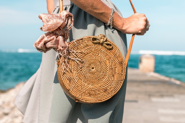 A woman wearing a grey skirt and a brown rattan bag standing by the ocean