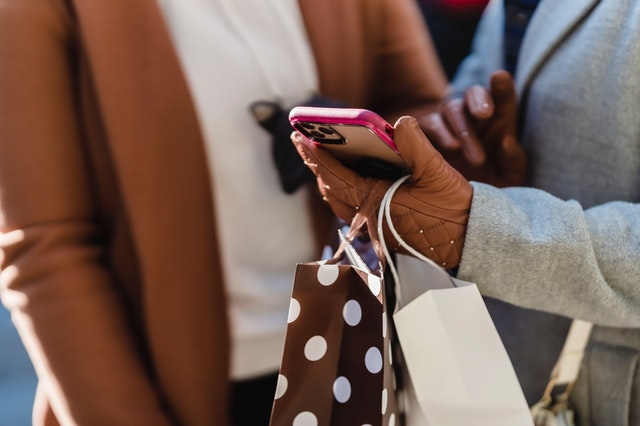 Two women shopping together on a smartphone