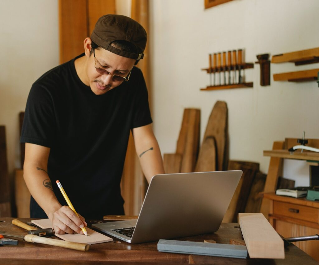 Carpenter working and taking notes next to a laptop