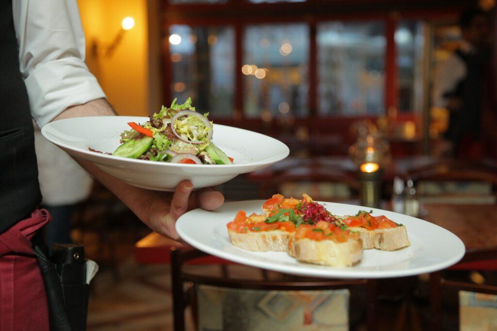 A waiter holding plates at a restaurant