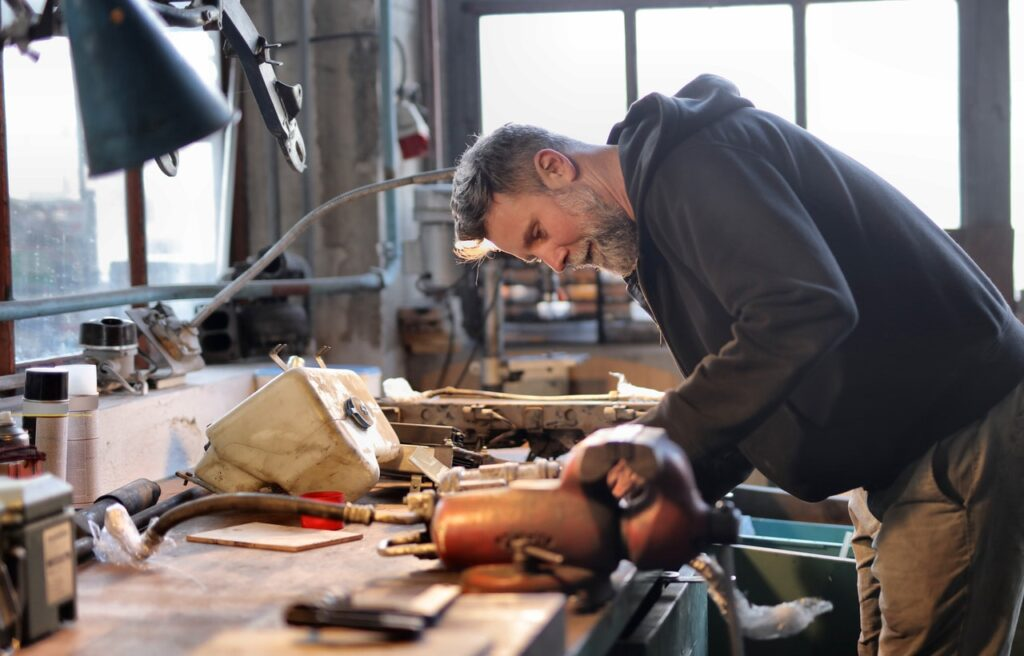 Mechanic working in a garage, validating his idea before he commits to this small business full time.